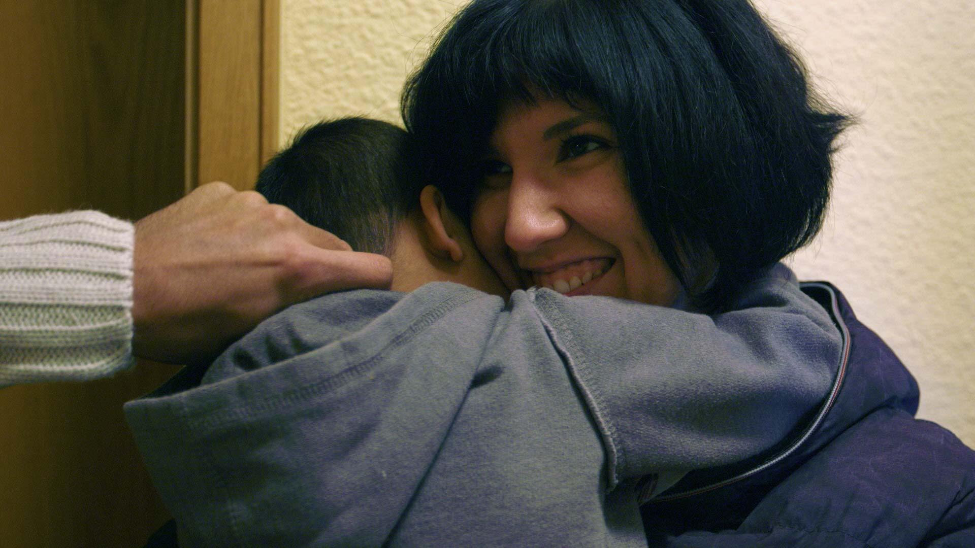 Junge Frau wird von einem syrischen Kind umarmt