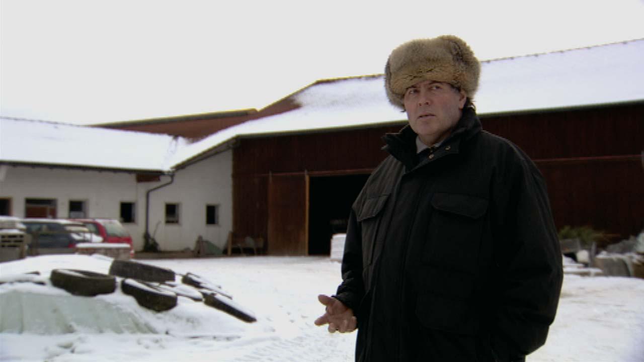 Ein gläubiger Landwirt steht vor seinem Hof