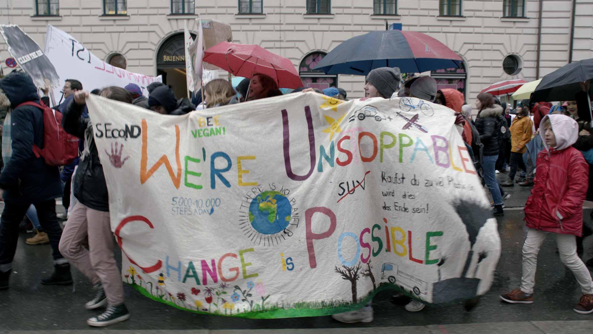 we are unstoppable - change is possible - junge Aktivisten tragen ein Transparent
