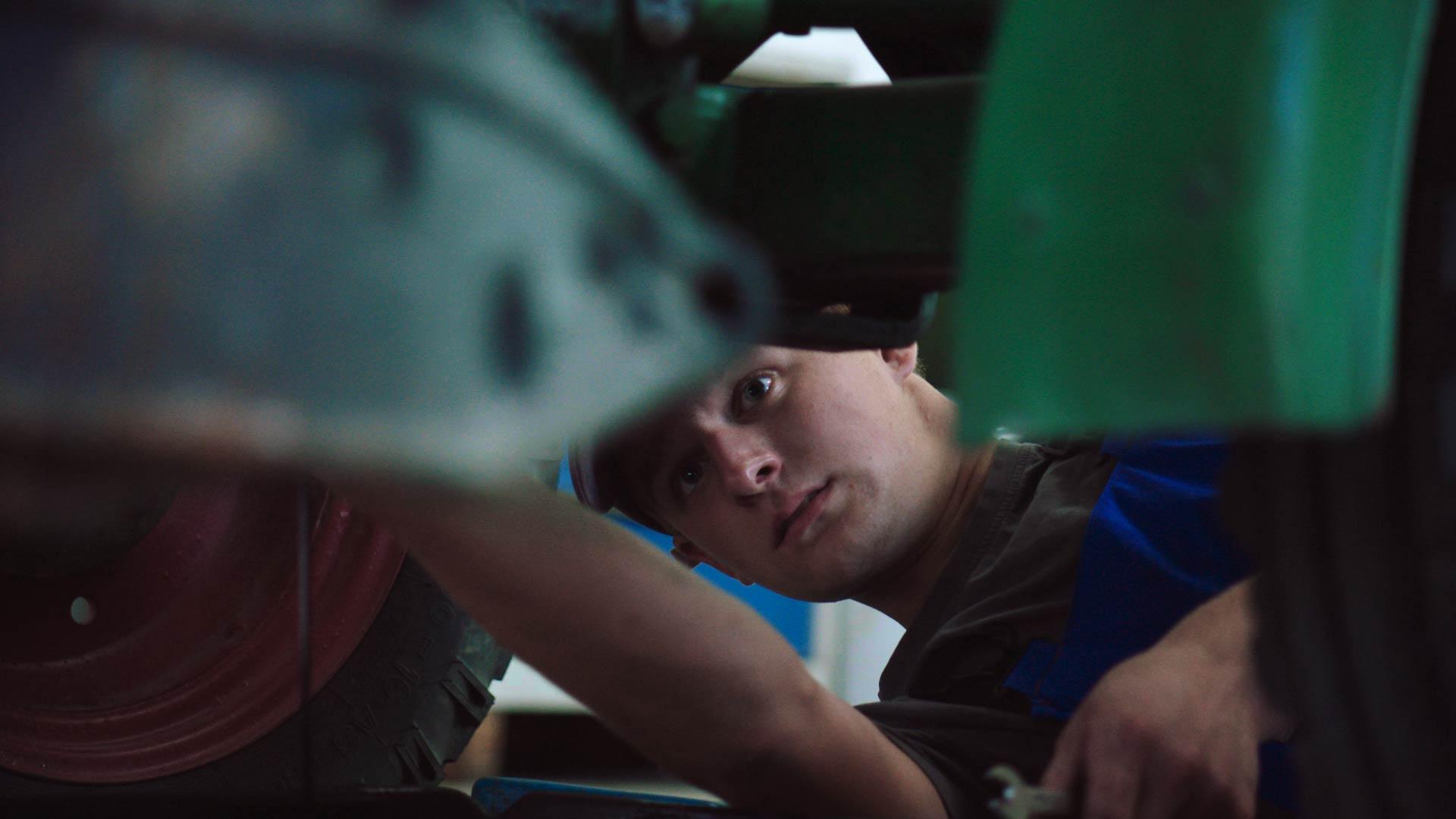 junger Mann beim Ölwechsel unter einem Traktor