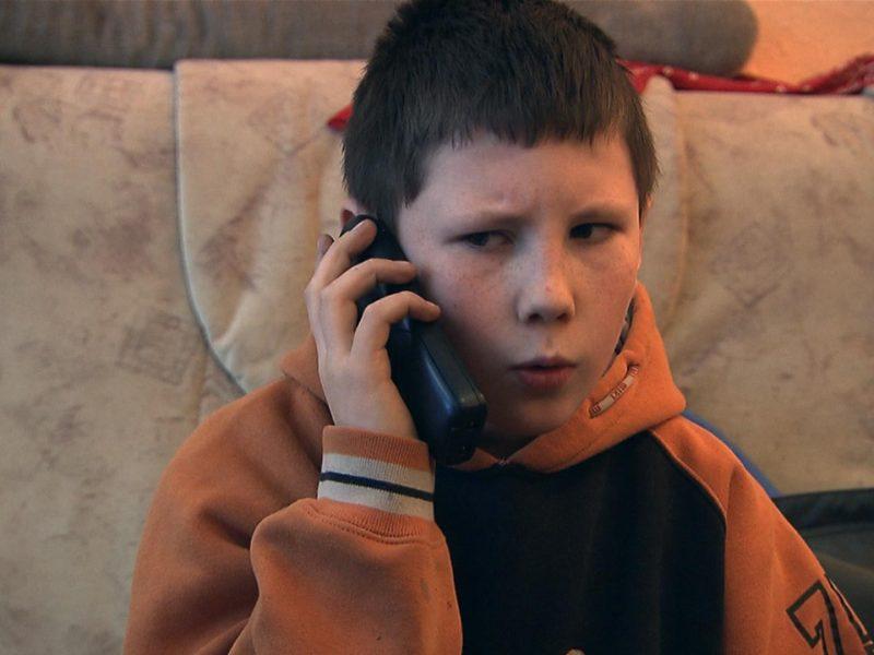 Junge telefoniert morgens mit seiner Mutter