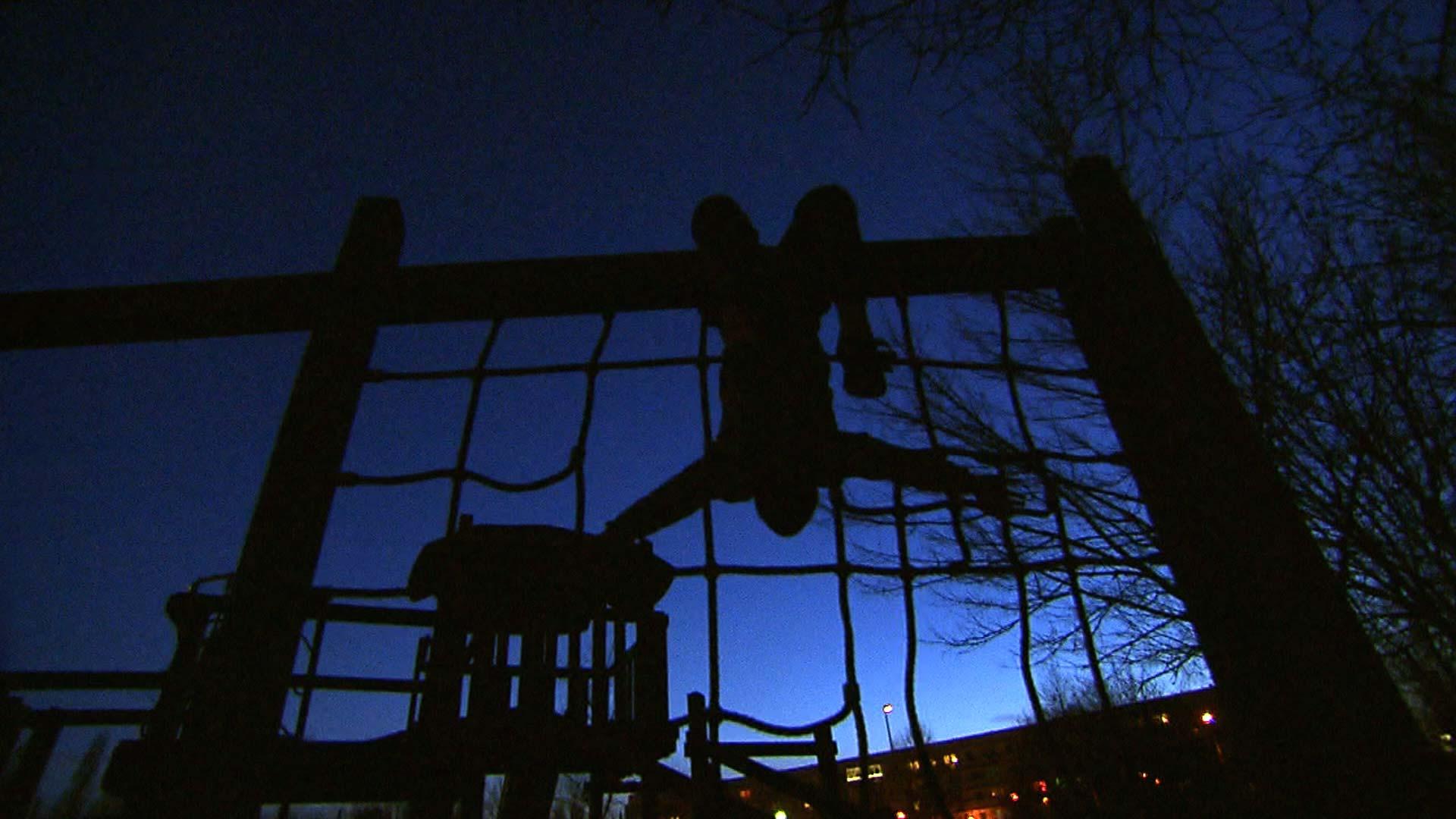Junge spielt nachts auf dem Spielplatz