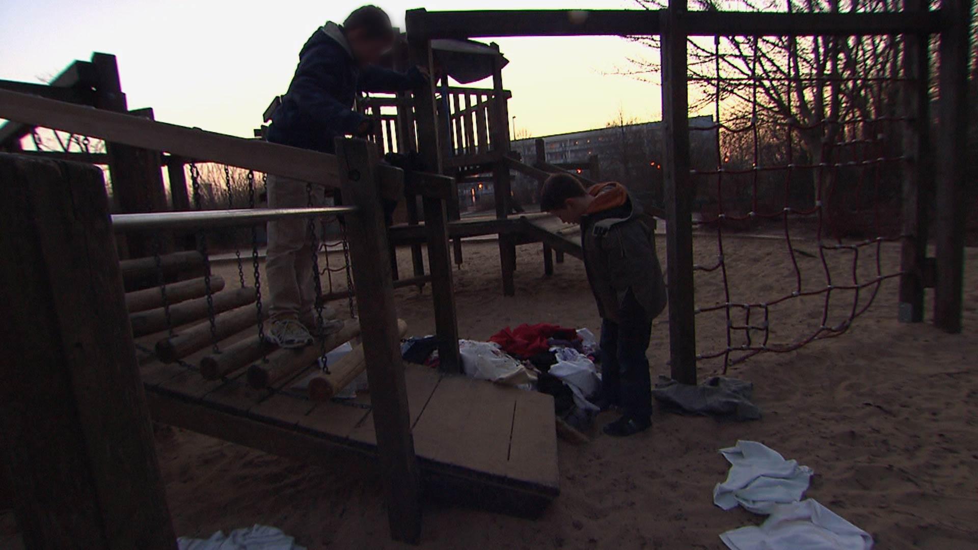 Junge findet abends ein Kleiderdepot auf einem Spielplatz