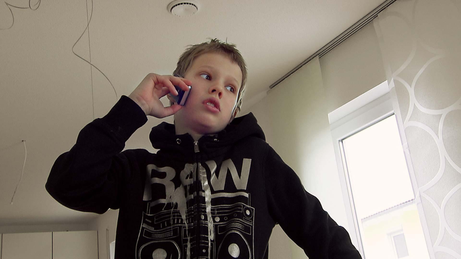 Junge telefoniert mit seinen Eltern
