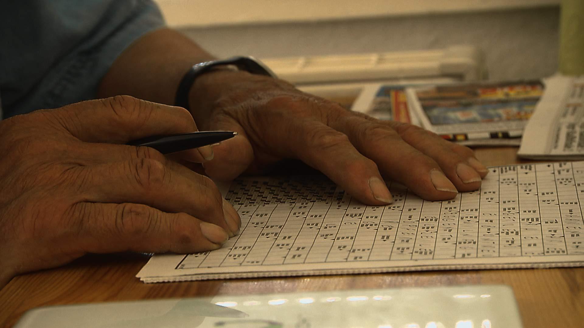 Alter Mann löst Kreuzworträtsel