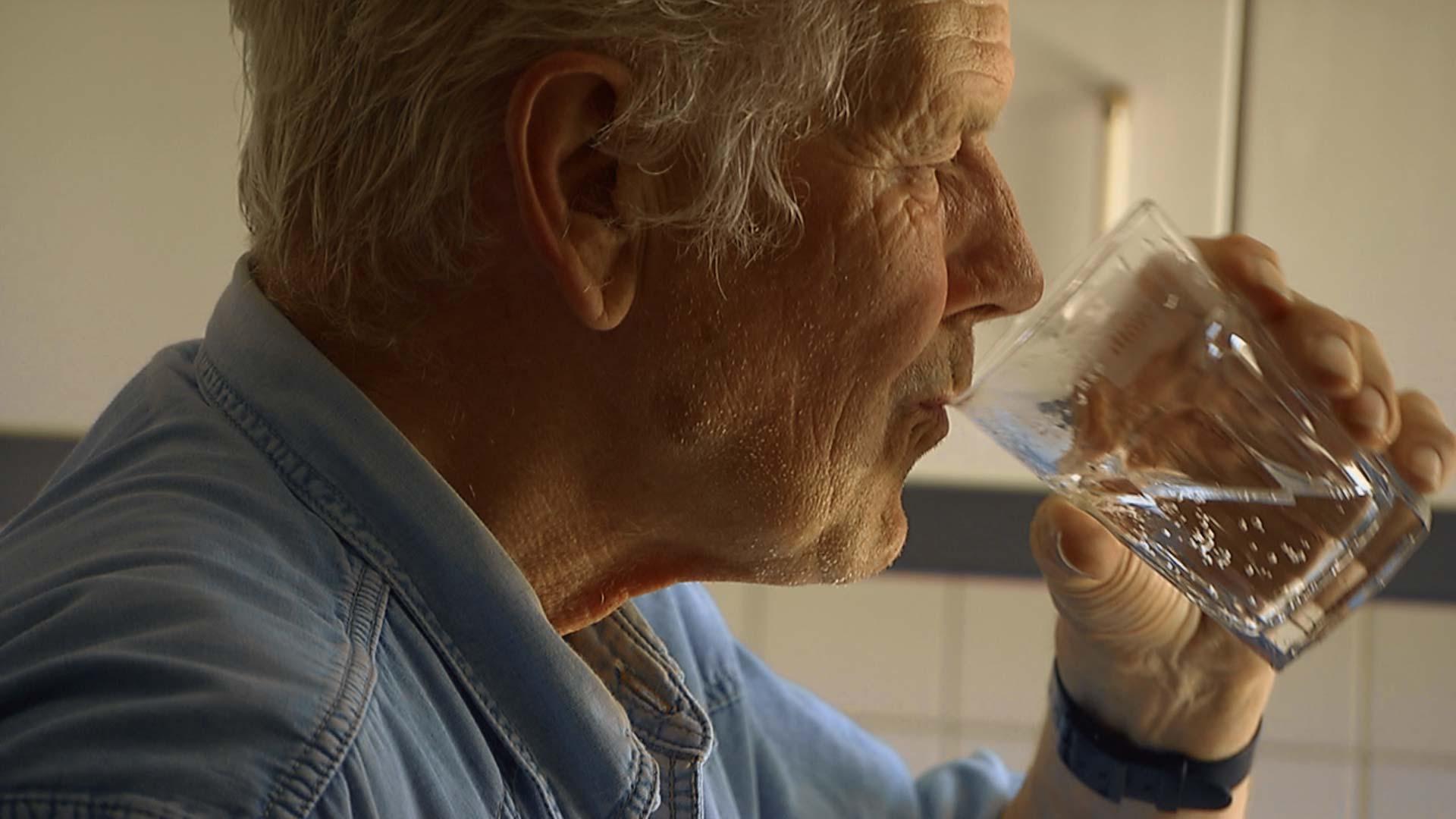 Alter Mann trinkt ein Glas Wasser
