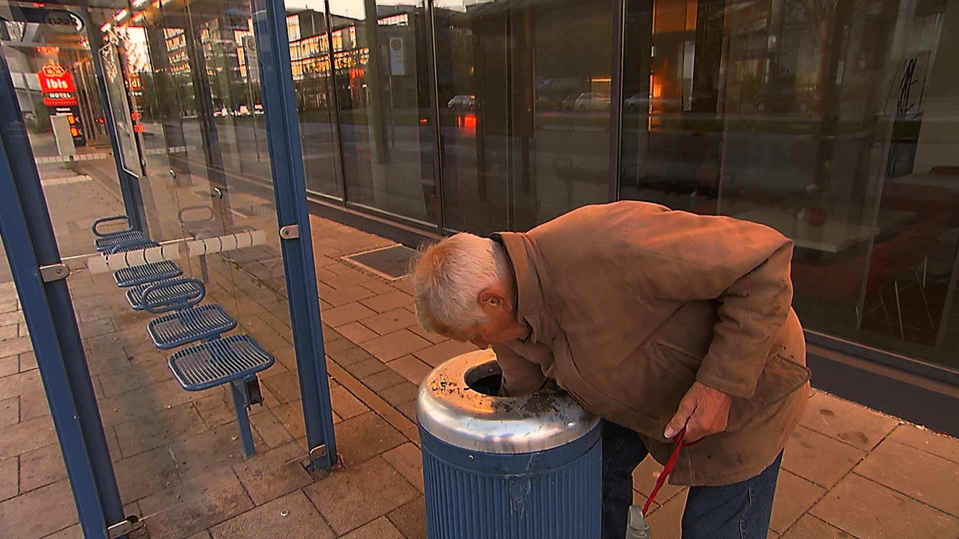 alter Mann sucht nach Flaschen in einem Mülleimer