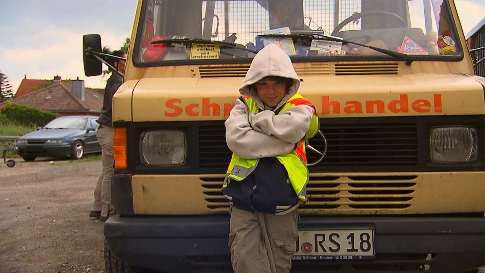Kind vor LKW mit Aufschrift Schrotthandel