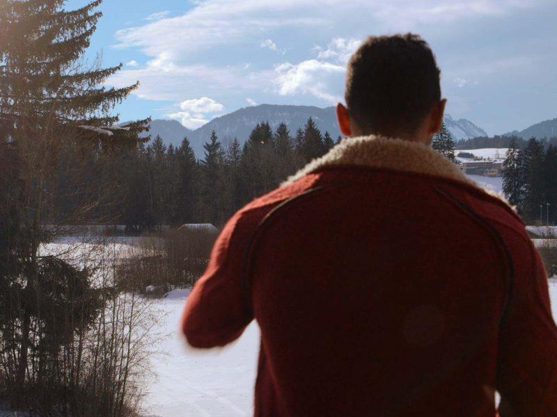 geflüchteter Syrer blickt in die Alpenkulisse