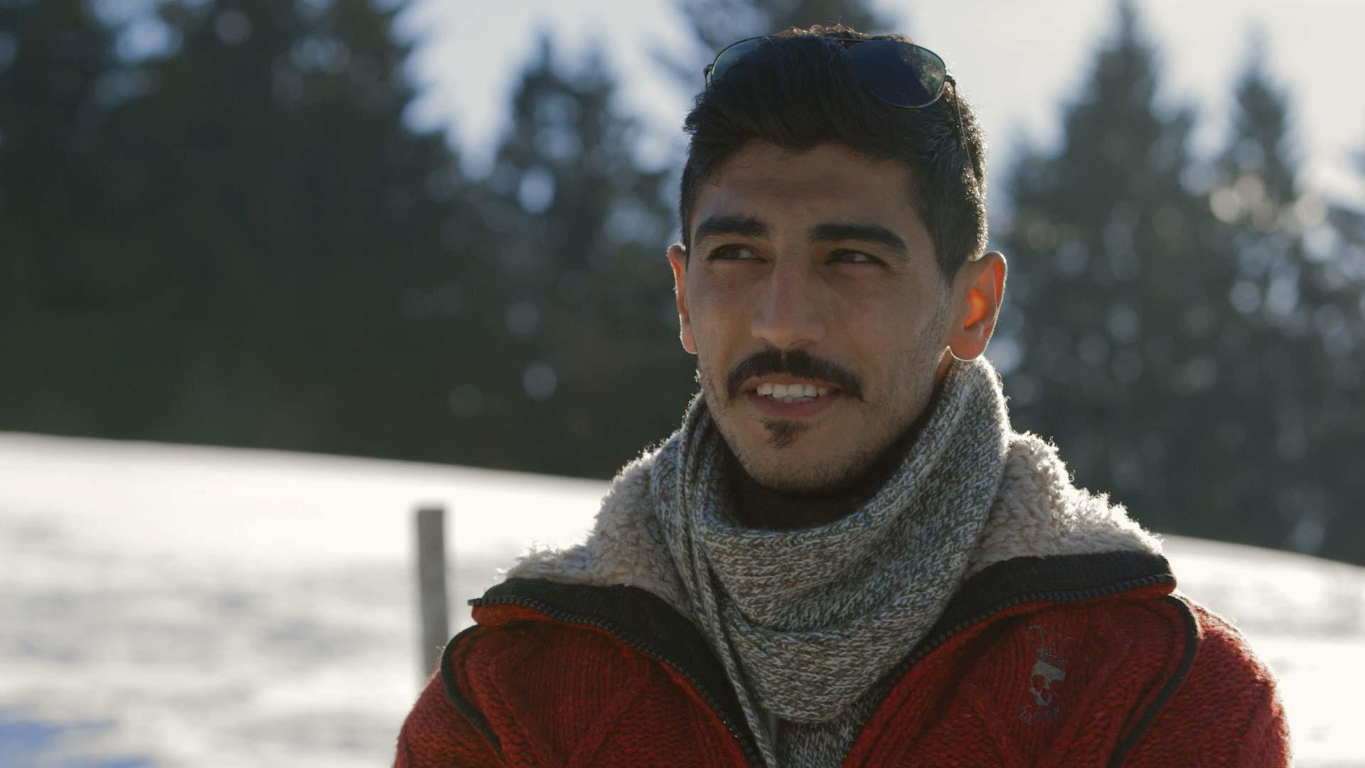 geflüchteter Syrer vor verschneiter Landschaft