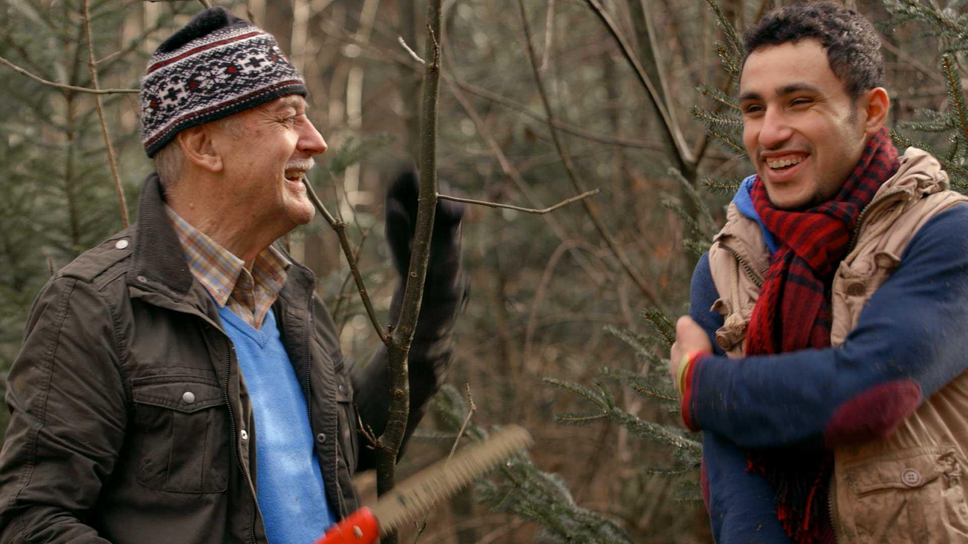 Geflüchteter mit Einheimischem bei der Arbeit im Wald