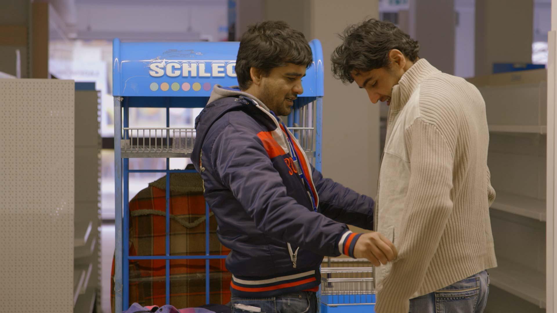 zwei geflüchtete Afghanen in der Kleiderkammer
